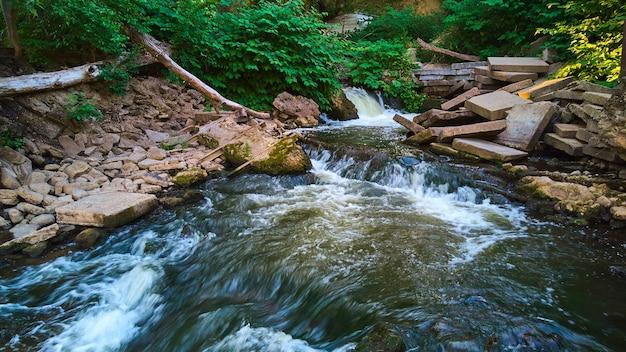 Image de piles de carreaux de ciment autour de la rivière avec des cascades et des plantes vertes
