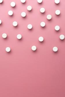 Image de pilules blanches sur fond rose. espace de copie. lay plat. composition verticale.