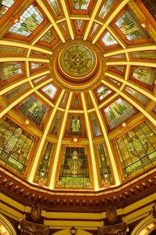 Image de plafond multicolore et rococo avec de petits vitraux aux lignes jaunes convergeant vers une lucarne centrale