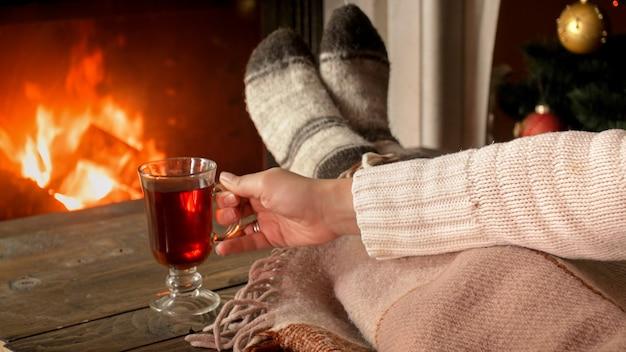 Image de plan rapproché tonique de jeune femme tenant la tasse de thé à la cheminée brûlante dans le salon