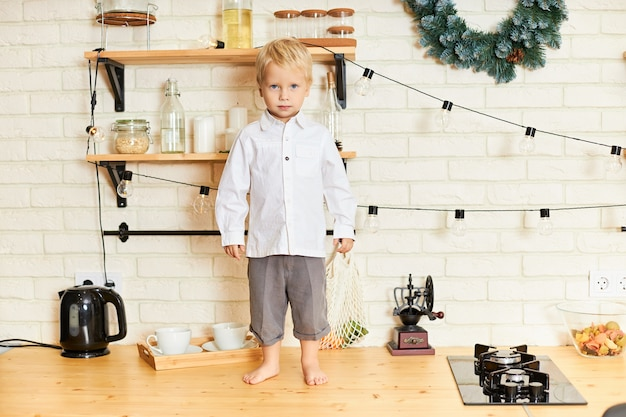 Image pleine longueur d'adorable petit garçon aux cheveux blonds debout pieds nus sur une table en bois dans un intérieur élégant de cuisine scandinave avec une couronne de noël, se conduisant mal alors que personne ne le voit