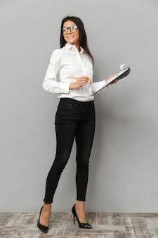 Image pleine longueur de belle femme portant une tenue professionnelle et des lunettes tenant le presse-papiers avec des papiers, tout en regardant de côté isolé sur fond gris