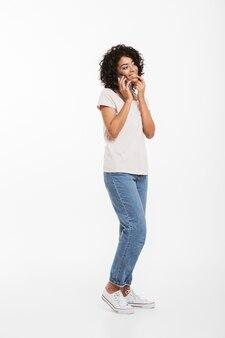 Image pleine longueur de contenu femme américaine avec une coiffure afro portant un t-shirt et un jean parlant au téléphone portable avec plaisir, isolé sur un mur blanc