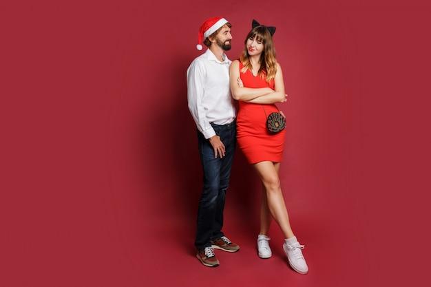 Image pleine longueur d'un couple élégant amoureux en chapeaux de mascarade de nouvel an debout sur rouge.