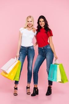 Image pleine longueur de deux femmes souriantes étreignant avec des paquets dans les mains et regardant la caméra sur rose