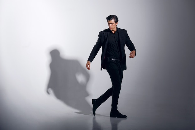 Image pleine longueur du beau modèle masculin en costume élégant noir, isolé sur fond blanc. vue horizontale.
