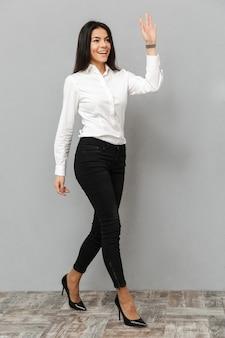 Image pleine longueur de femme d'affaires heureuse en chemise blanche et pantalon noir marche et salutation avec agitant la main, isolé sur fond gris