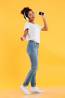 Image pleine longueur de femme africaine heureuse dansant et écoutant de la musique