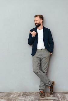 Image pleine longueur d'un homme barbu souriant en vêtements de travail tenant le bras dans la poche tout en pointant et en regardant au-dessus de gris