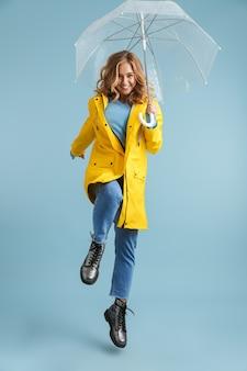 Image pleine longueur de jeune femme de 20 ans portant un imperméable jaune debout sous un parapluie transparent