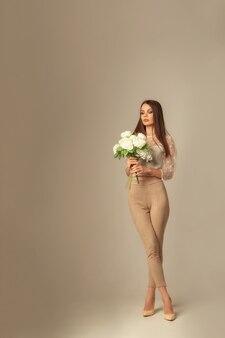 Image pleine longueur d'une jeune femme brune avec des fleurs posant et regardant l'avant sur une surface beige