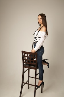 Image pleine longueur d'une jeune femme brune vêtue d'un chemisier blanc, d'un jean et d'un harnais posant sur la chaise et regardant l'avant sur une surface beige
