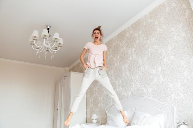 Image pleine longueur de jeune femme s'amusant sur le lit