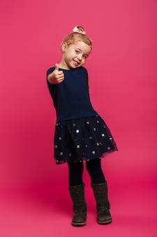 Image pleine longueur de jeune fille blonde souriante montrant le pouce vers le haut et regardant la caméra sur le mur rose