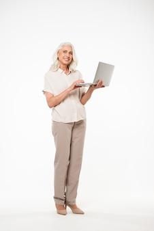 Image pleine longueur de mamie adulte mature des années 60 avec des cheveux gris souriant et tenant un ordinateur portable d'argent à la main, isolé sur un mur blanc