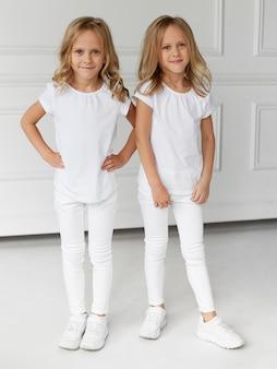 Image pleine longueur d'un sourire de petites filles d'enfants en vêtements blancs