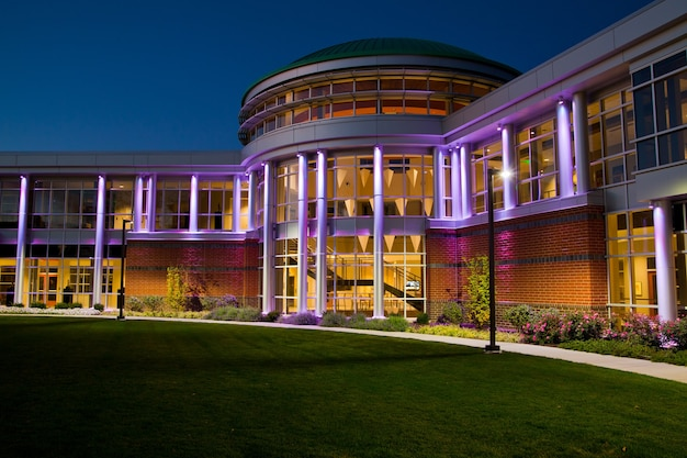 Image de la porte d'entrée du bâtiment moderne avec de nombreuses fenêtres au crépuscule allumé en violet