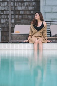 Image portrait d'une belle femme asiatique apprécié assis au bord de la piscine