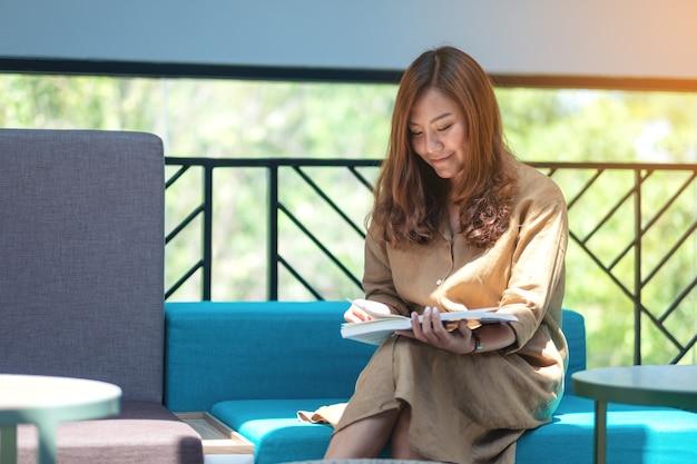 Image portrait d'une belle femme asiatique assise et lisant un livre