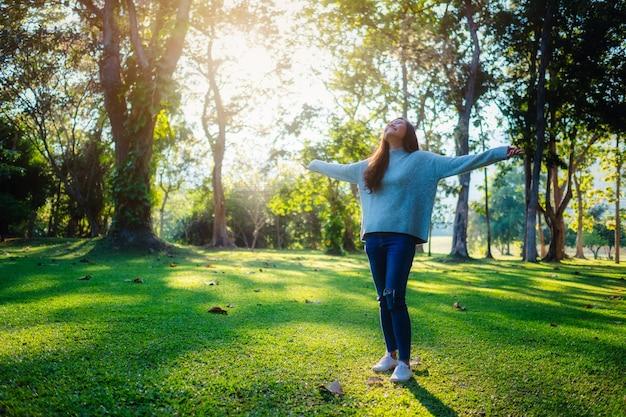 Image portrait d'une belle femme asiatique debout et ouvrant les bras au milieu de la nature dans le parc avant le coucher du soleil