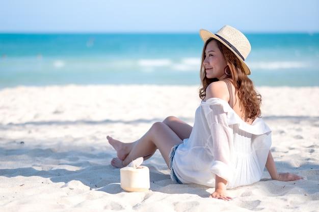 Image portrait d'une belle femme asiatique profiter de s'asseoir et de boire du jus de noix de coco sur la plage