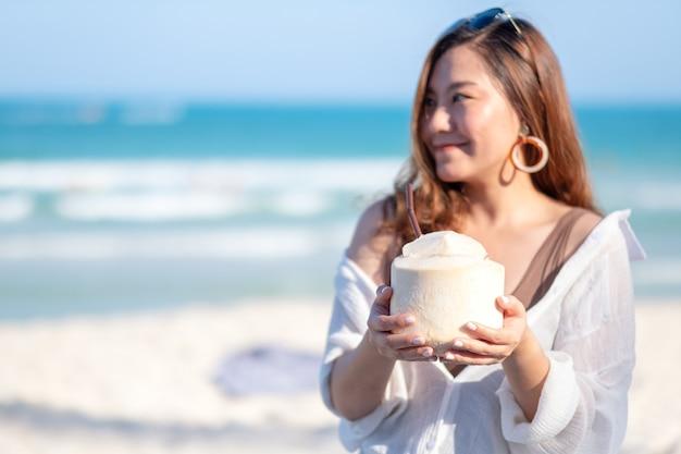 Image portrait d'une belle femme asiatique tenant et boire du jus de noix de coco sur la plage