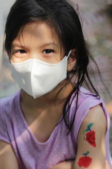 Image portrait de l'école primaire asiatique petite fille portant un masque pour la prévention des coronavirus