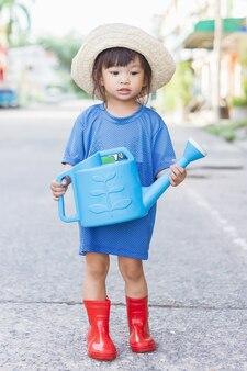 Image de portrait de fille enfant de 3-4 ans. fille d'enfant asiatique heureuse arrosant l'arbre vert par l'eau peut à son arrière-cour. jardinage en été ou au printemps. activité des enfants. notion d'apprentissage.