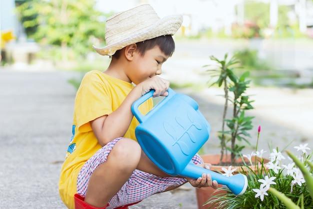 Image de portrait d'un garçon de 7-8 ans. heureux enfant asiatique arrosant l'arbre vert et les fleurs par l'eau peut à l'arrière-cour. jardinage en été ou au printemps. activité des enfants.