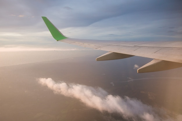 L'image qui regarde à travers la fenêtre sur l'avion supérieur volant dans le ciel