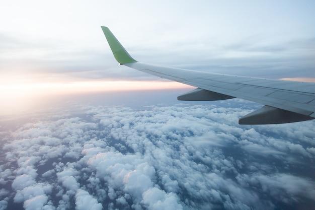 Image qui regarde à travers la fenêtre sur l'avion supérieur volant dans le ciel