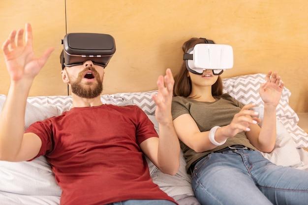Image réaliste. surpris doux couple émotionnel agitant les mains en position couchée et en utilisant des casques vr