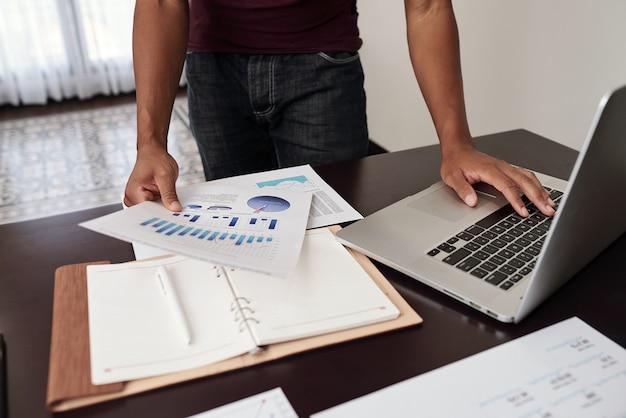 Image recadrée d'analyste financier vérifiant les rapports avec des graphiques et des diagrammes sur son bureau