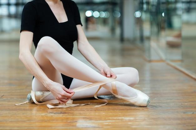 Image recadrée d'une ballerine attachant des pointes en cours de ballet