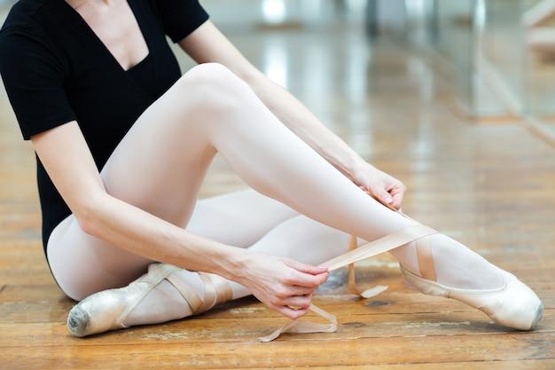 Image recadrée d'une ballerine habillant des pointes en cours de ballet