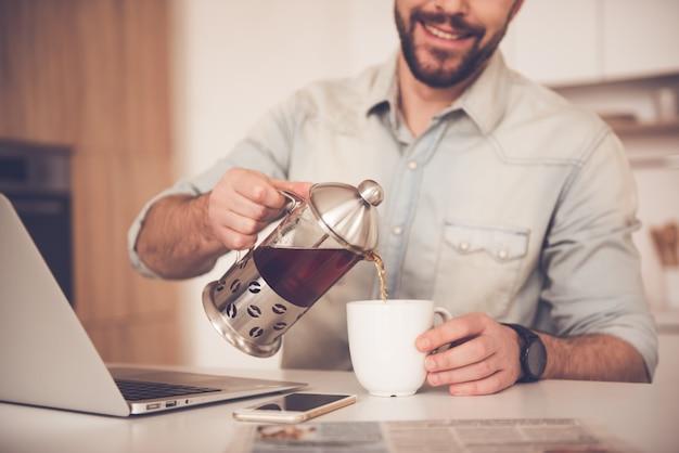 Image recadrée de bel homme d'affaires versant le thé.