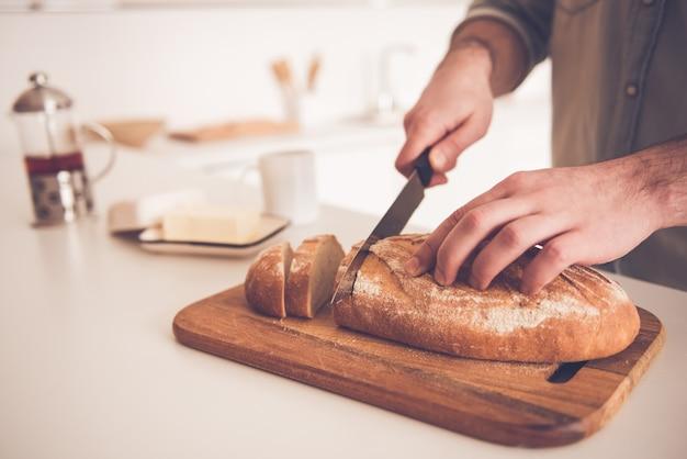 Image recadrée de bel homme coupe du pain.