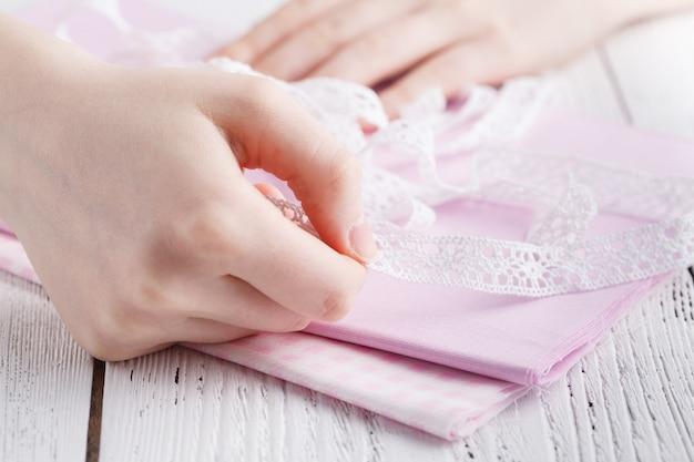 Image recadrée de la belle jeune designer travaillant avec des croquis et du ruban à mesurer dans un salon de couture