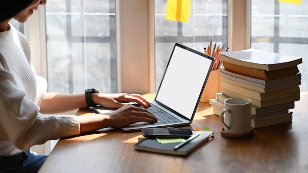Image recadrée de la belle jeune femme travaillant comme écrivain en tapant sur ordinateur portable avec écran blanc.