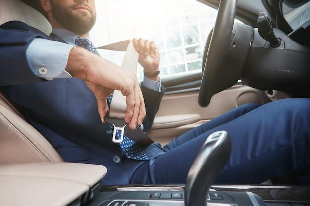 Une image recadrée de conduite sûre d'un jeune homme d'affaires en tenue de soirée attache la ceinture de sécurité