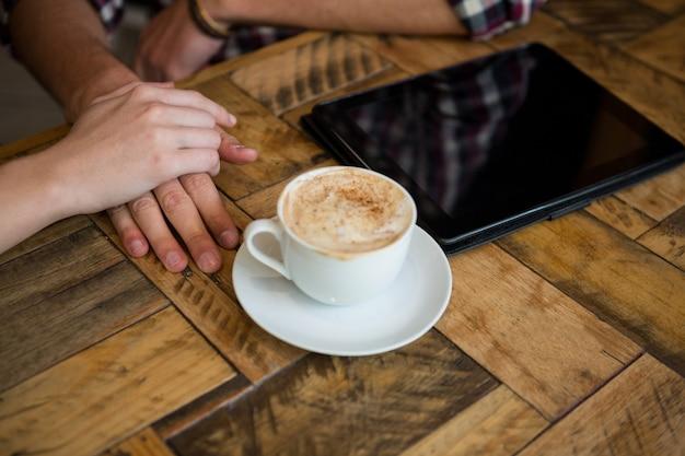 Image recadrée de couple main dans la main avec une tasse de café et un tablet pc sur table in cafe