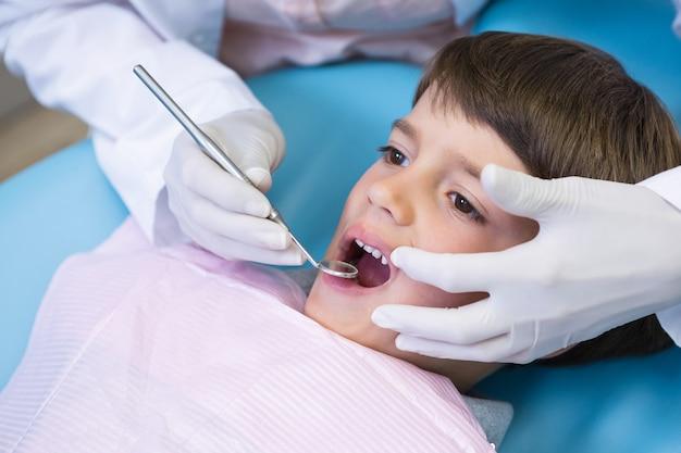 Image recadrée de dentiste tenant l'équipement lors de l'examen de garçon