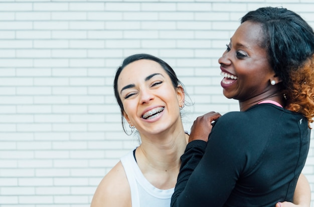 Image recadrée de deux femmes se tenant la main. la main à gauche est celle d'une jeune femme blanche. celui de droite vient d'une jeune femme noire.