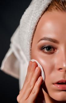 Image recadrée du visage la jeune fille tient un coton sur son visage fond gris concept de beauté