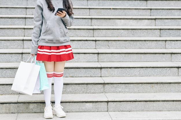 Image recadrée d'une écolière coréenne en jupe courte et chaussettes hautes debout sur les marches avec des sacs à provisions dans les mains et un ami texto