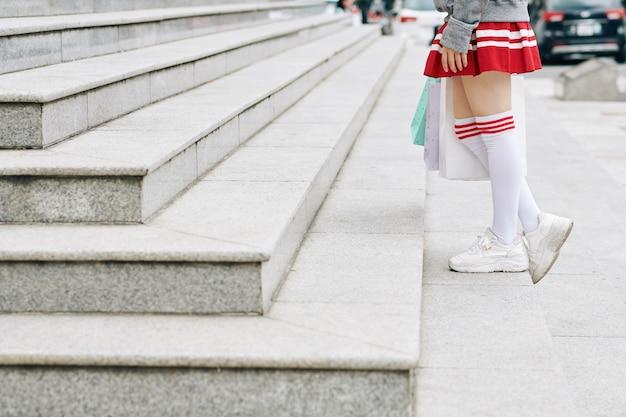 Image recadrée d'une écolière en jupe courte et chaussettes hautes montant les escaliers avec des sacs à provisions dans les mains