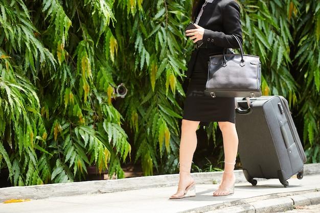 Image recadrée d'une femme d'affaires marchant dans la rue jusqu'au terminal de l'aéroport ou à la gare avec une valise