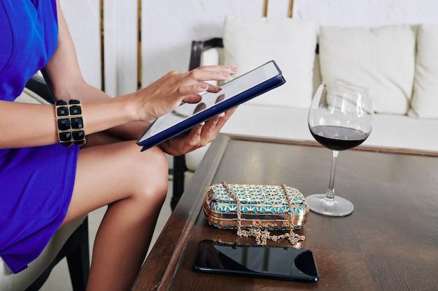Image recadrée de femme d'affaires en robe de cocktail, boire du bon vin et à l'aide de l'application sur tablette