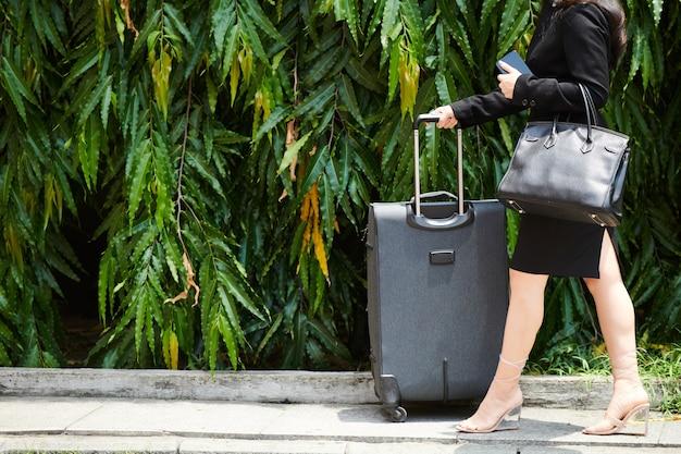 Image recadrée d'une femme d'affaires en talons hauts marchant dans la rue avec une grosse valise et un sac