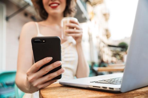 Image recadrée de femme au chapeau de paille à l'aide de smartphone